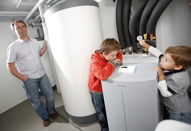 Homme se tenant à côté d'une pompe à chaleur en compagnie de ses enfants